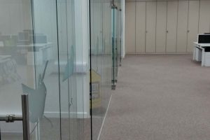 Open plan office with glass partitions and storage wall